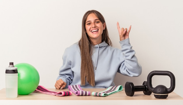 Giovane donna caucasica seduta a un tavolo con attrezzature sportive isolato su sfondo bianco che mostra un gesto di corna come un concetto di rivoluzione.