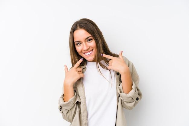 La giovane donna caucasica sorride, indicando le dita alla bocca.