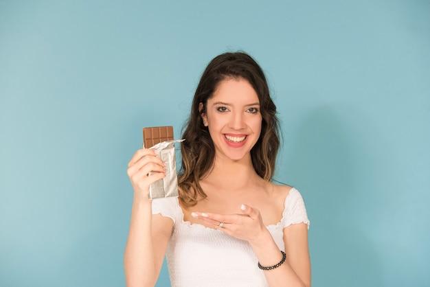 Giovane donna caucasica sorridente con barretta di cioccolato chocolate