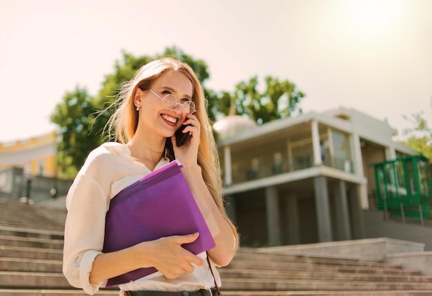 Giovane studentessa caucasica in abbigliamento casual con esse nella cartella parlando al telefono scendendo le scale