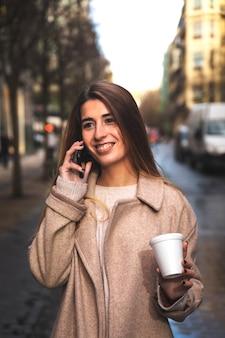Giovane donna caucasica parlando al telefono mentre beve il caffè