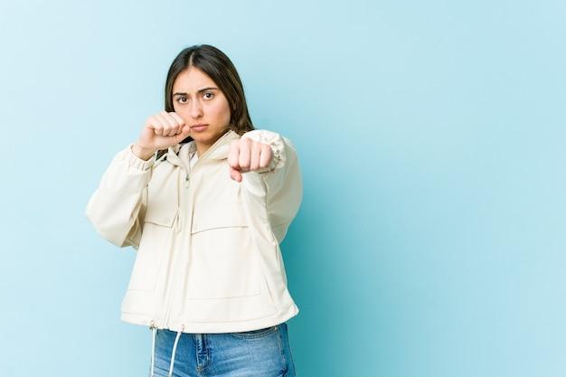 Giovane donna caucasica che lancia un pugno, rabbia, combattimenti a causa di un argomento, boxe.