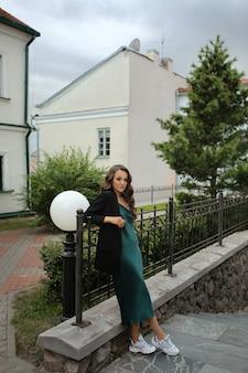 Giovane donna caucasica in abito verde alla moda e giacca in posa sul tramonto nella strada di una città europea