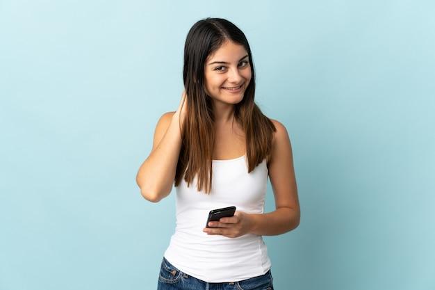 Giovane donna caucasica utilizzando il telefono cellulare isolato sulla parete blu ridendo