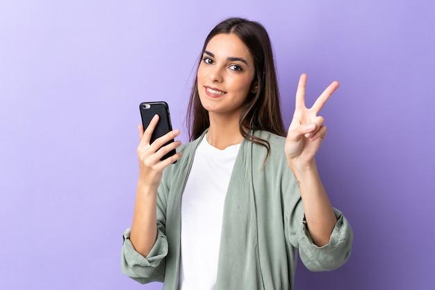 Giovane donna caucasica utilizzando il telefono cellulare isolato su viola sorridente e mostrando il segno di vittoria