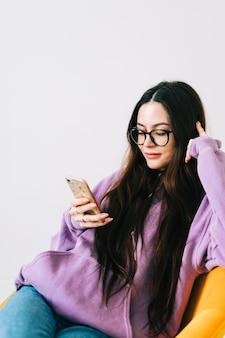 Giovane donna caucasica utilizzando il telefono cellulare, seduto sulla poltrona nel soggiorno.