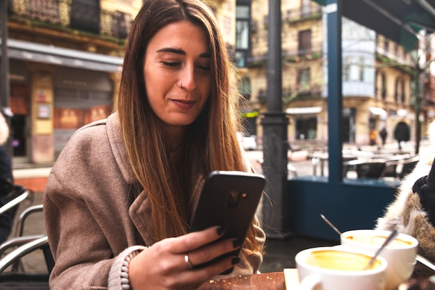 Giovane donna caucasica utilizzando un telefono cellulare mentre si consuma la colazione su una terrazza in una mattina d'inverno