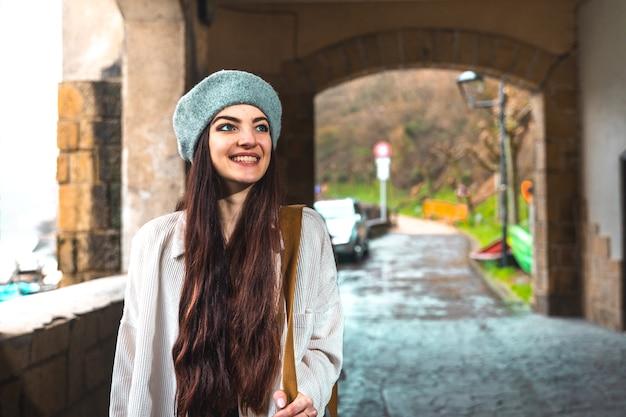 Giovane donna caucasica che visita una vecchia città sul lato del fiume