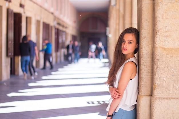 Giovane donna caucasica che cammina attraverso il centro della città