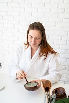 Giovane donna caucasica che indossa accappatoi facendo procedure termali utilizzando cosmetici naturali