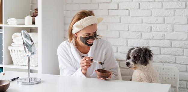 Giovane donna caucasica che indossa accappatoi facendo procedure termali con il suo cane