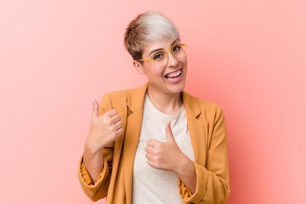 La giovane donna caucasica che indossa un business casual copre alzando entrambi i pollici, sorridendo e fiducioso