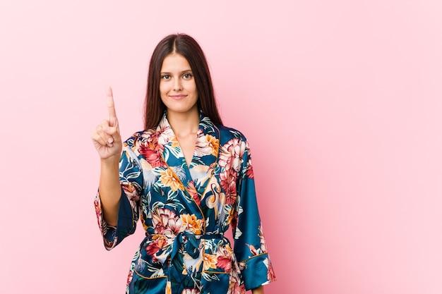 Giovane donna caucasica che indossa un pigiama kimovero che mostra il numero eccessivo con il dito.
