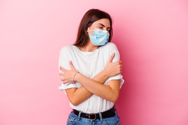 Giovane donna caucasica che indossa una maschera per virus isolata su sfondo rosa abbraccia, sorride spensierata e felice.