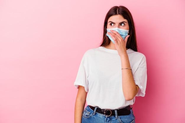 Giovane donna caucasica che indossa una maschera per virus isolato sulla parete rosa premurosa guardando uno spazio di copia che copre la bocca con la mano.