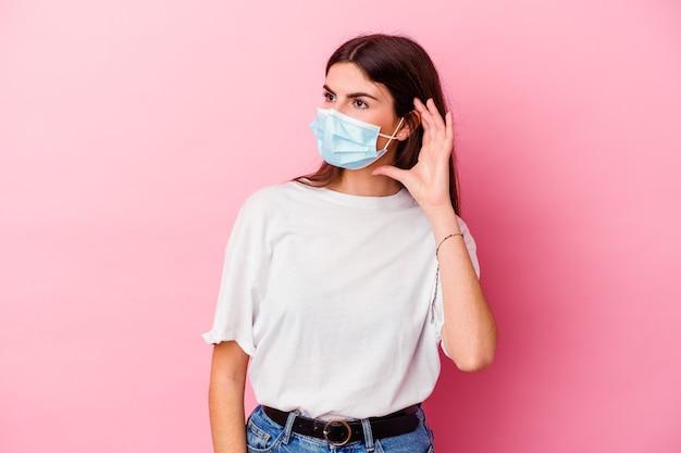 Giovane donna caucasica che indossa una maschera per virus isolato sulla parete rosa, cercando di ascoltare un pettegolezzo.