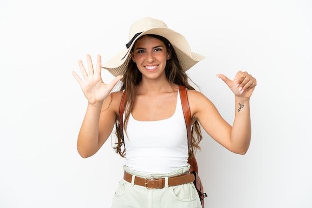 Giovane donna caucasica che indossa una pamela durante le vacanze estive isolate su sfondo bianco contando sei con le dita