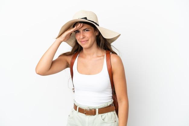 Giovane donna caucasica che indossa una pamela durante le vacanze estive isolate su sfondo bianco guardando lontano con la mano per guardare qualcosa