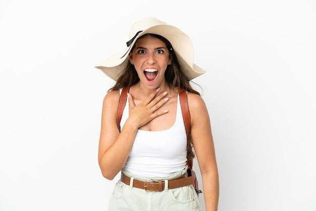 Giovane donna caucasica che indossa una pamela durante le vacanze estive isolata su sfondo bianco con espressione facciale sorpresa e scioccata