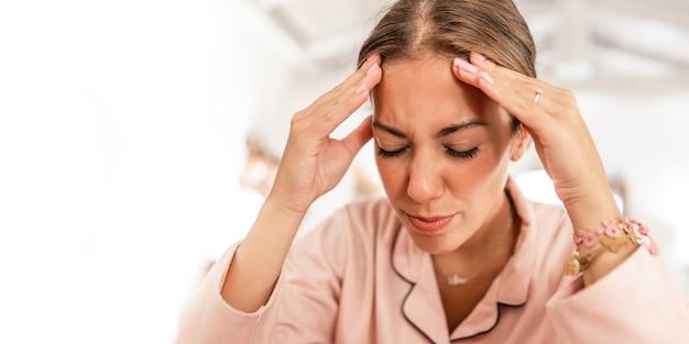 Una giovane donna caucasica che indossa il pigiama rosa tiene la testa tra le mani e fa smorfie per il dolore dovuto all'emicrania