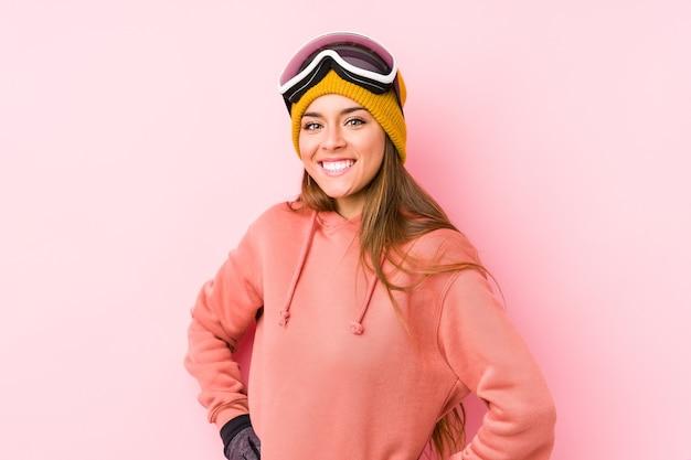 Giovane donna caucasica che indossa un abbigliamento da sci isolato sicuro mantenendo le mani sui fianchi.