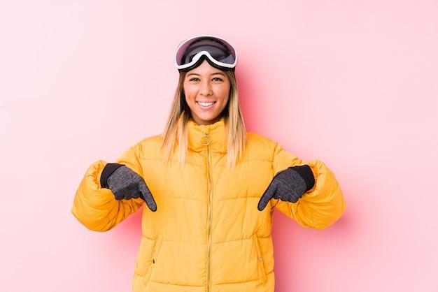 La giovane donna caucasica che indossa un abbigliamento da sci in uno spazio rosa punta verso il basso con le dita, sensazione positiva.