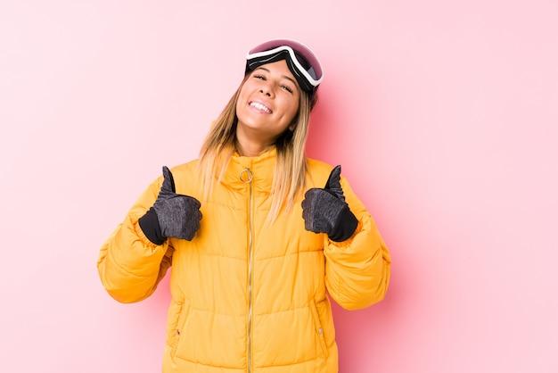 La giovane donna caucasica che indossa uno sci copre in una parete rosa che alza entrambi i pollici, sorridenti e sicuri.