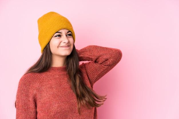 Giovane donna caucasica che indossa un berretto di lana toccando la parte posteriore della testa, pensando e facendo una scelta.