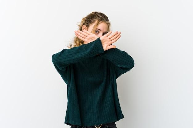 Giovane donna caucasica su backrgound bianco mantenendo due braccia incrociate, concetto di negazione.