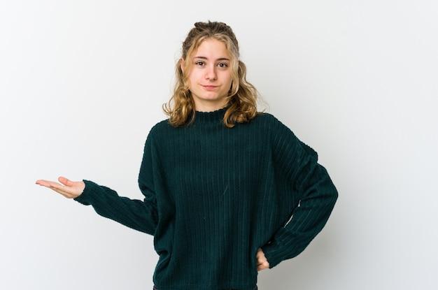 Giovane donna caucasica sul muro bianco dubitando e alzando le spalle nel gesto interrogativo.