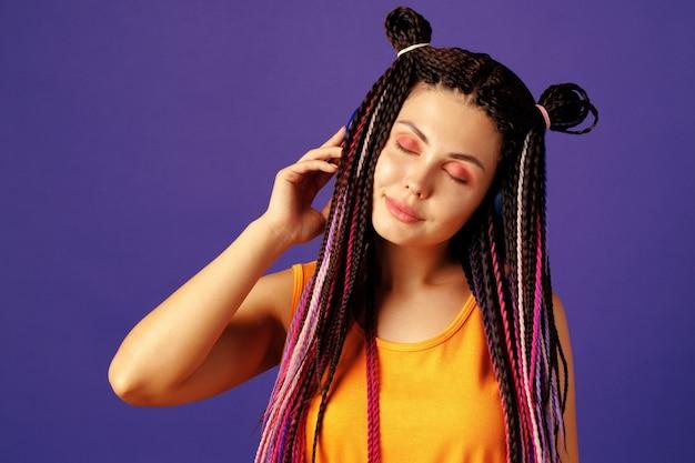 Giovane donna caucasica con treccine africane ascoltando musica con le cuffie