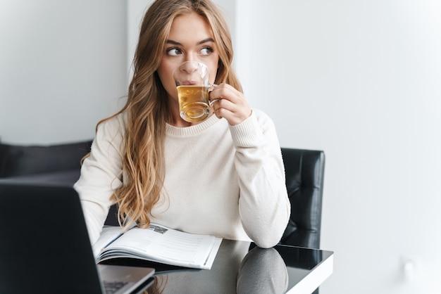 Giovane donna caucasica con i capelli biondi che beve tè e digita sul computer portatile mentre è seduto al tavolo