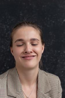 Giovane donna caucasica con capelli castani in giacca con catena sul collo che fa una faccia buffa. femmina che scherza davanti alla bandiera dello studio, facendo smorfie