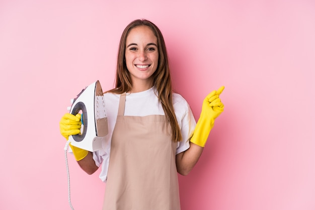 Giovane donna caucasica con vestiti di ferro isolato sorridendo e indicando da parte, mostrando qualcosa in uno spazio vuoto.