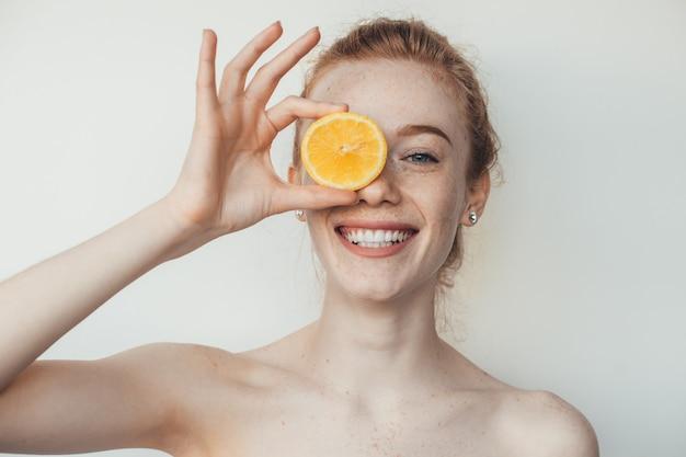 Giovane donna caucasica con lentiggini e capelli rossi si copre gli occhi con un limone e sorride su un muro bianco in posa con spalle nude