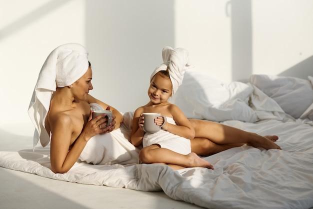 Una giovane donna caucasica con sua figlia su un letto a casa al mattino, indossando un asciugamano gioca e beve un latte