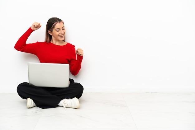 Giovane donna caucasica con un computer portatile che si siede sul pavimento che celebra una vittoria