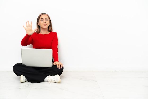 Giovane donna caucasica con un computer portatile seduto sul pavimento contando cinque con le dita