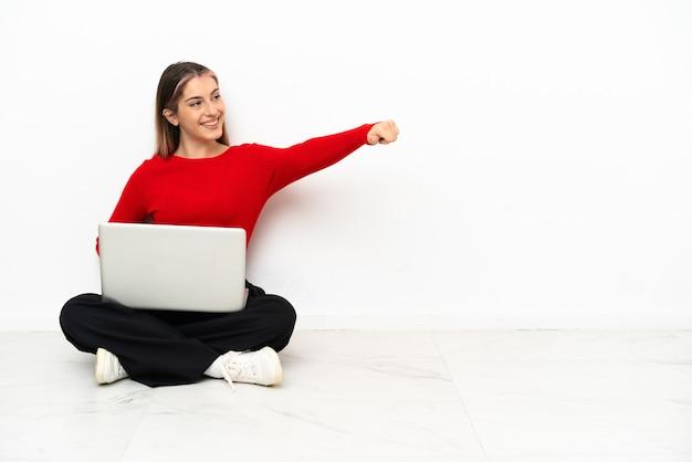 Giovane donna caucasica con un computer portatile che si siede sul pavimento che dà un pollice in alto gesto
