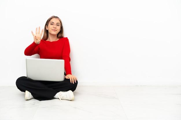 Giovane donna caucasica con un computer portatile che si siede sul pavimento felice e contando quattro con le dita