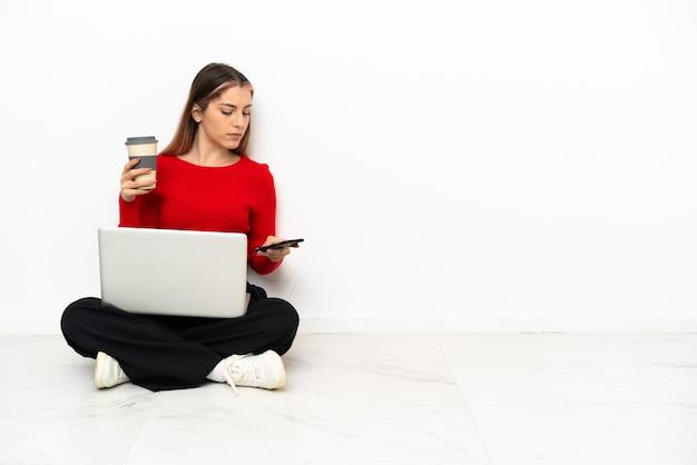 Giovane donna caucasica con un computer portatile che si siede sul pavimento che tiene il caffè da portare via e un cellulare