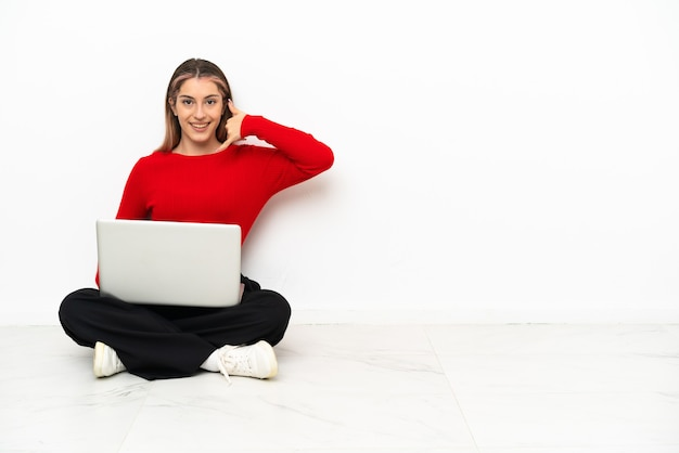 Giovane donna caucasica con un computer portatile che si siede sul pavimento che fa il gesto del telefono. richiamami segno