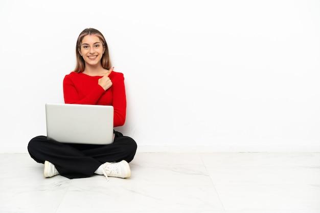 Giovane donna caucasica con un computer portatile seduto sul pavimento che punta di lato per presentare un prodotto