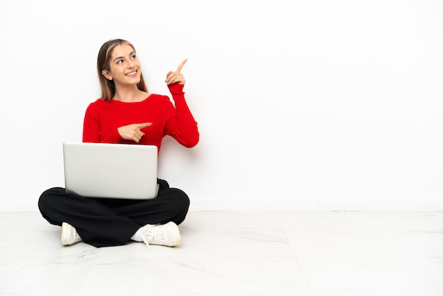 Giovane donna caucasica con un computer portatile che si siede sul pavimento che indica con il dito indice una grande idea