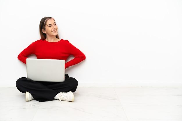 Giovane donna caucasica con un computer portatile seduto sul pavimento in posa con le braccia al fianco e sorridente