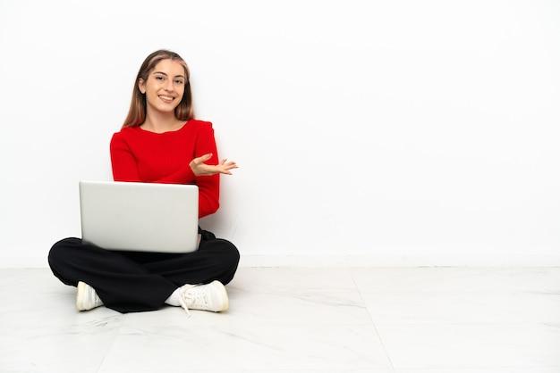 Giovane donna caucasica con un laptop seduto sul pavimento che presenta un'idea mentre guarda sorridente verso