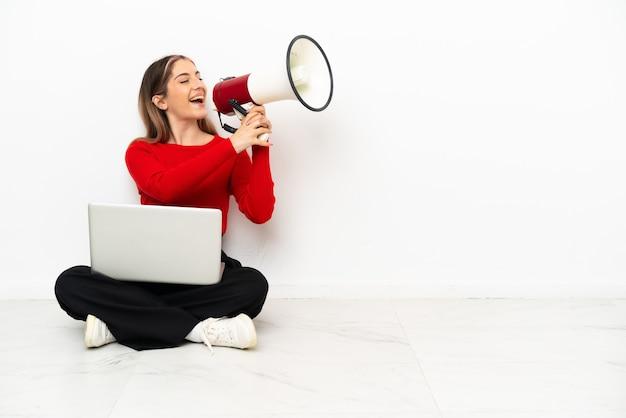 Giovane donna caucasica con un computer portatile che si siede sul pavimento che grida tramite un megafono
