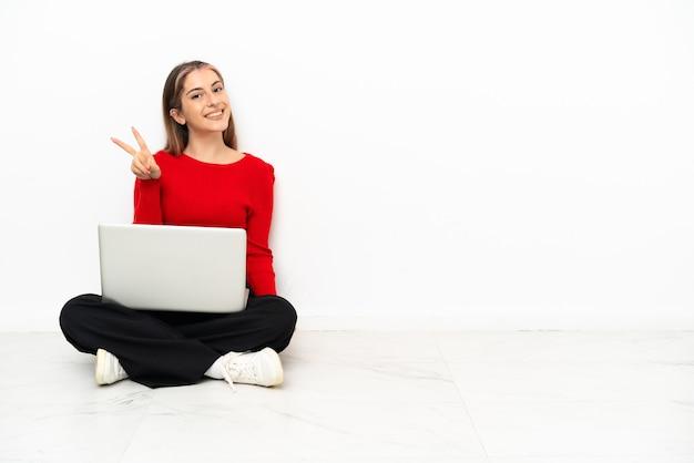 Giovane donna caucasica con un computer portatile che si siede sul pavimento che sorride e che mostra il segno di vittoria