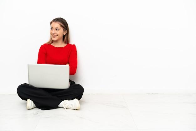 Giovane donna caucasica con un computer portatile seduto sul pavimento con le braccia incrociate e felice