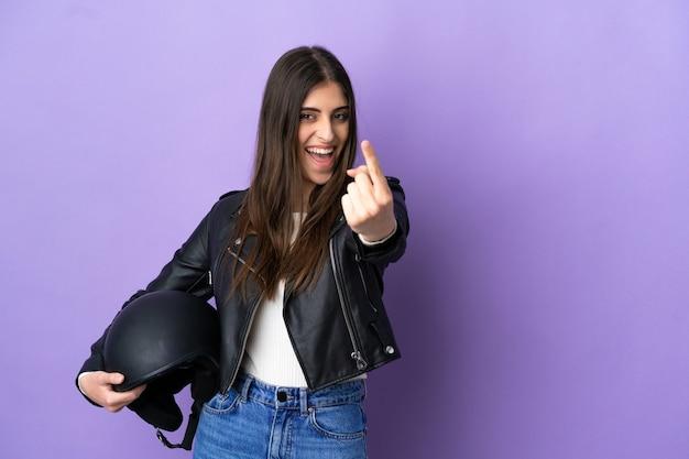 Giovane donna caucasica con un casco da motociclista isolato su sfondo viola che fa un gesto imminente